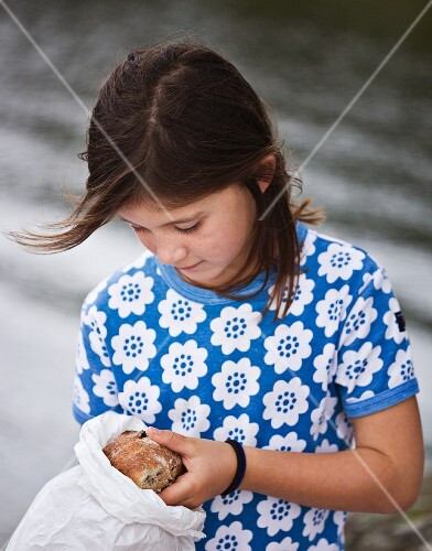 A girl taking a bread roll out of a paper bag