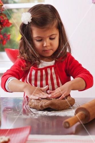 Little girl kneading gingerbread dough