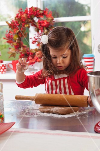 Little girl rolling out gingerbread dough