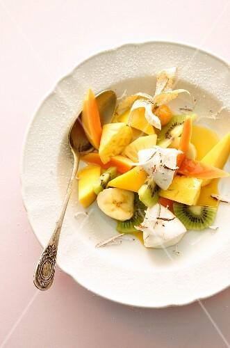 A fruit salad with yogurt dumplings and coconut