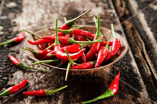 A wooden bowl of red chilli peppers