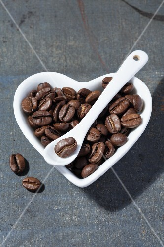 Coffee beans in a heart-shaped porcelain bowl with a porcelain spoon