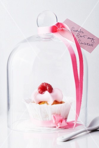 A raspberry muffin under a cloche decorated with a love letter and bow