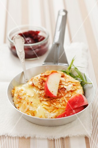 Baked camembert with an almond crust and apples served with cranberry jelly