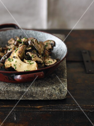 Sauteed Mushrooms in a Pan on a Stone Slab