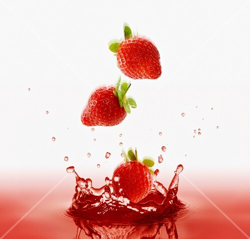 Strawberries falling into red juice