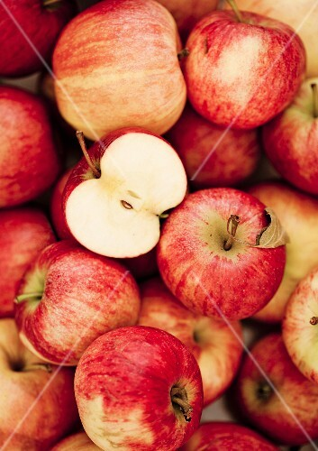 Lots of red apples, some have been halved