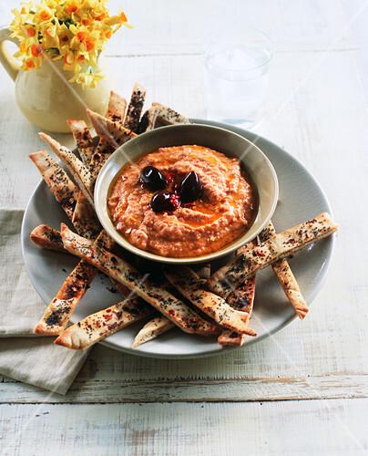 Pepper and tomato hummus with pita bread sticks