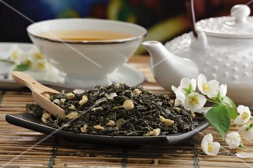 Dried green tea with jasmine blossom and a cup of jasmine tea