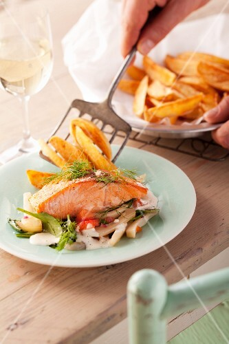 Salmon fillet on vegetables with chips
