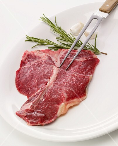 Raw T-bone steak with carving fork, rosemary and garlic