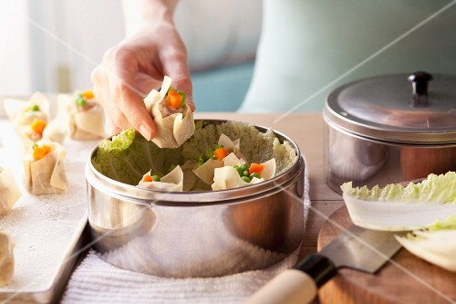 Won tons and Chinese cabbage leaves being place in a steamer