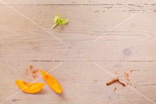 Pumpkin wedges and cinnamon on a wooden surface