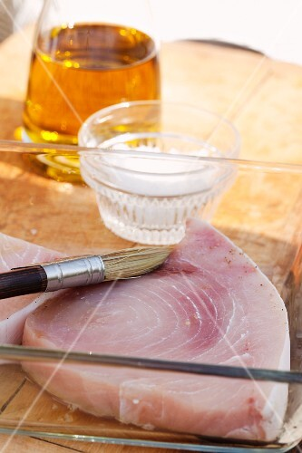 Swordfish steak being brushed with olive oil