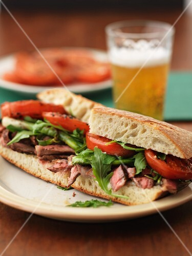 Sandwich with beef steak, tomatoes and rocket