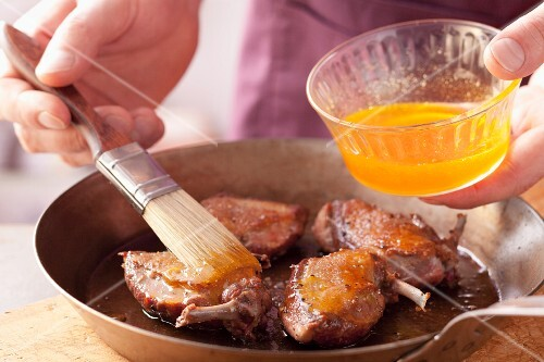 Basting fried pigeon breasts with orange glaze
