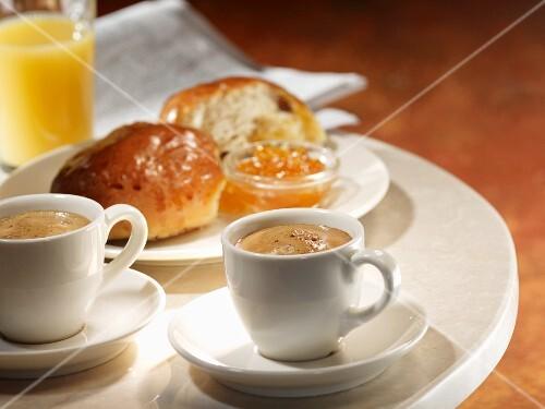 Two cups of espresso with brioche, jam and orange juice