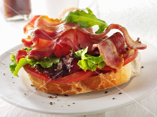 A slice of baguette topped with bacon, lettuce and tomato