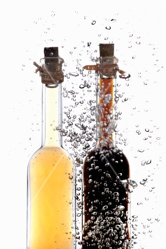 Vinegar and oil bottles in water with air bubbles