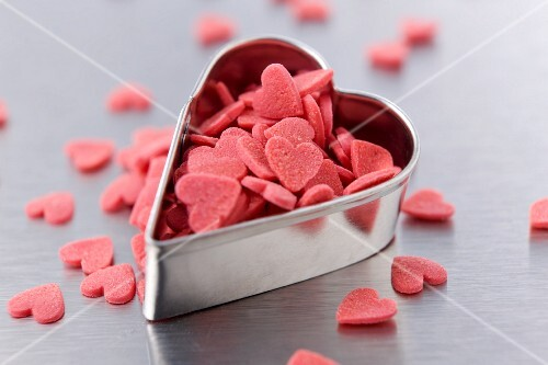 Heart-shaped cookie cutter and sugar hearts