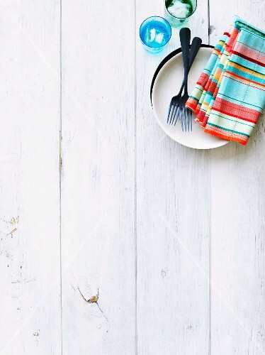 Plate with fork and colorful serviettes on a white wood background