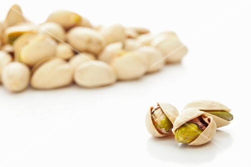 Toasted pistachios against a white background
