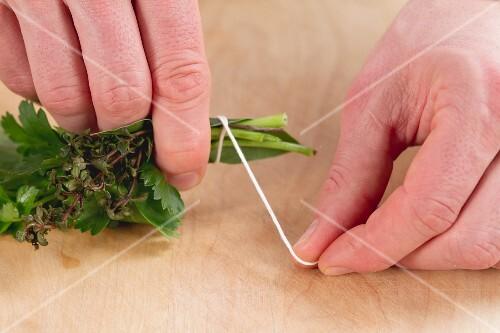 Kräuterstäusschen mit Küchengarn zusammenbinden
