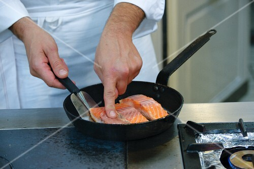 A chef frying salmon fillets