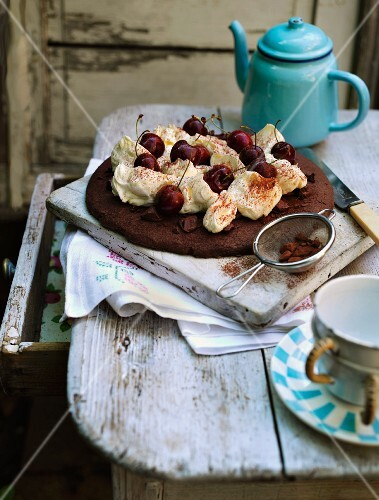 Luxurious chocolate cake with whipped cream and sweet cherries