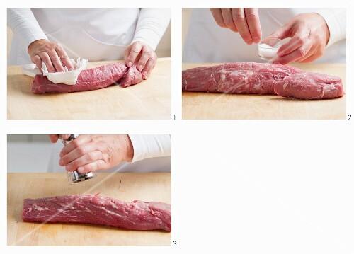 Veal fillet being seasoned