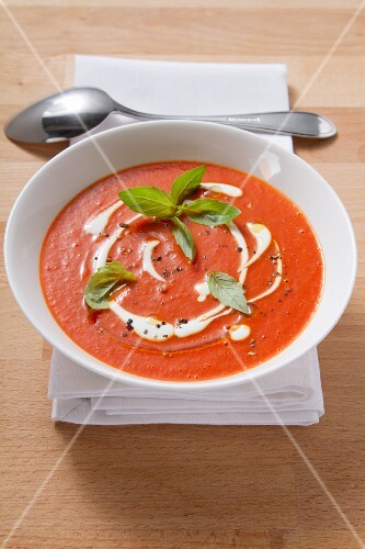 Cream of tomato soup garnished with creme fraiche and basil