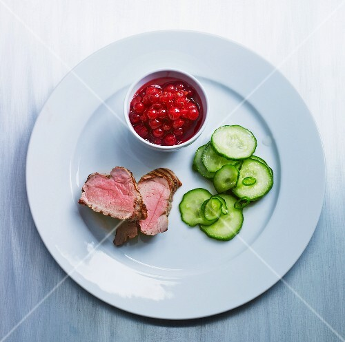 Medium-rare pork fillet with cucumber and cranberries