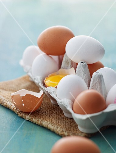 White and brown eggs in an egg box