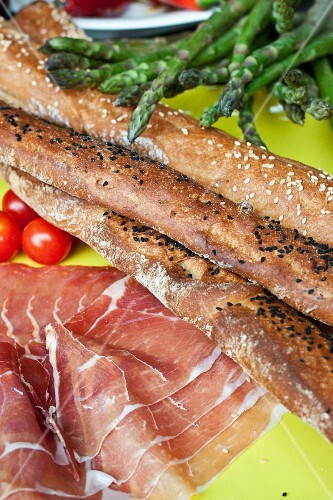 Bread sticks, raw ham, green asparagus and cherry tomatoes