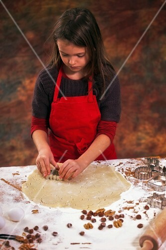A girl cutting out biscuits