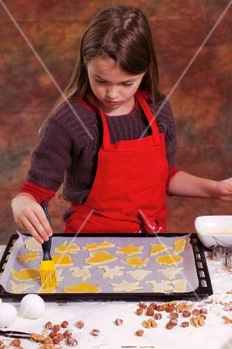 A girl brushing biscuits on a baking tray with egg yolk