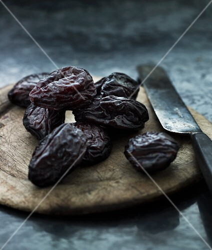 Prunes on a wooden board with a knife