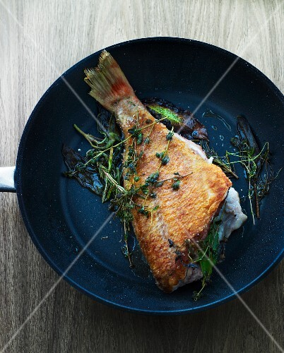 Fried fish with herbs in a pan (seen from above)