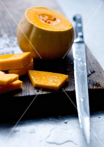 A sliced pumpkin with a knife on a wooden board