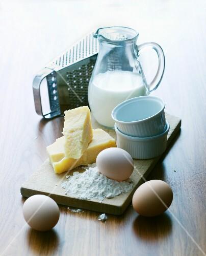 An arrangement of souffle ramekins, eggs, cheese, a cheese grater and milk