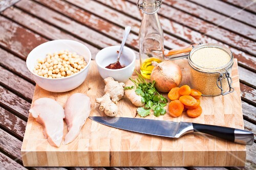 Chicken breast, vegetables and spices on a chopping board