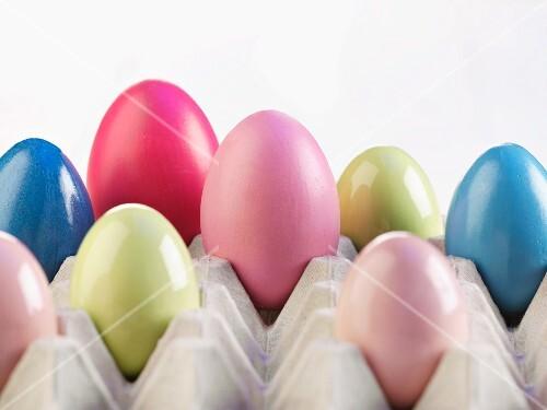 Coloured eggs in an egg box