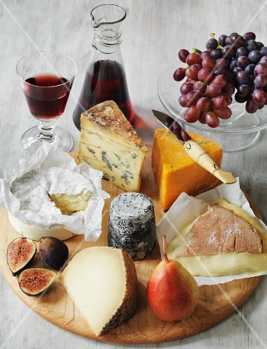 Various types of English cheese with fruit and wine