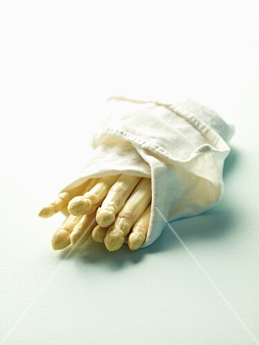 Peeled white asparagus wrapped in a cloth
