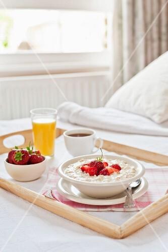 A breakfast tray on a bed (porridge with strawberries, coffee, orange juice)