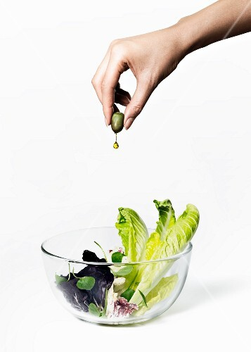 A hand squeezing olive oil from an olive onto a salad