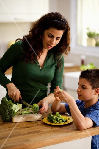 A mother and son preparing broccoli in the kitchen
