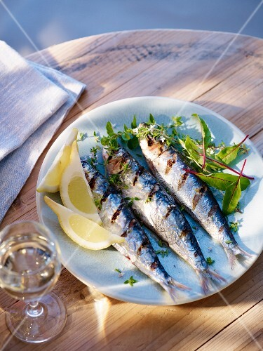 Grilled sardines with lemon wedges