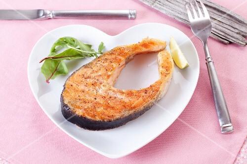 A salmon steak on a heart-shaped plate