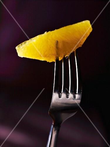An orange fillet on a fork